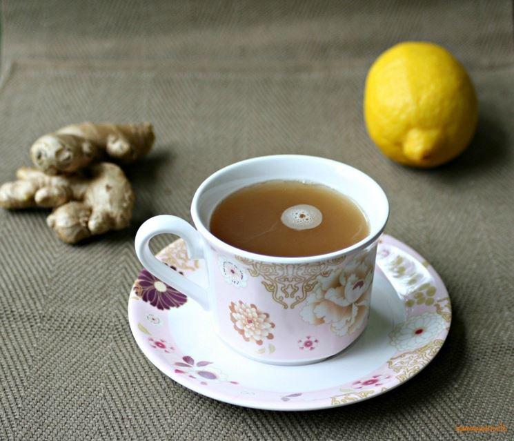 Tazza di decotto di zenzero con accanto pezzi di radici e un limone