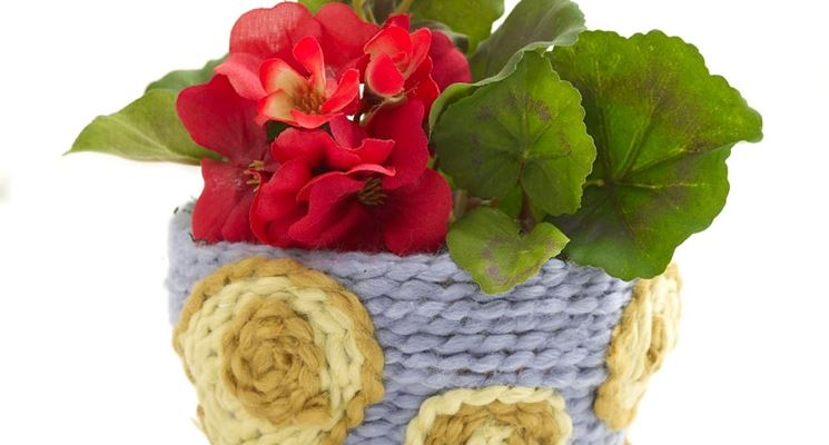 un vaso decorato da un lavoro ad uncinetto