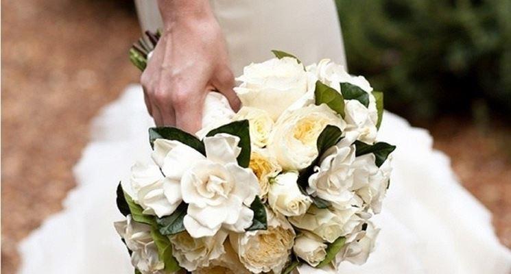 Bouquet di gardenie nelle mani di una sposa in bianco