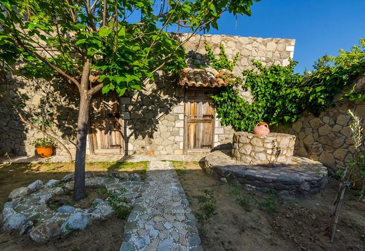 Giardino privato con vialetto e aiuole in pietra